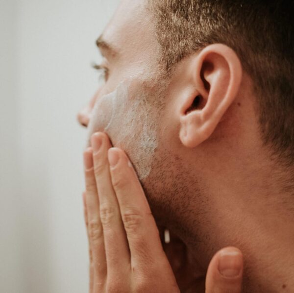 applying cream to mans face
